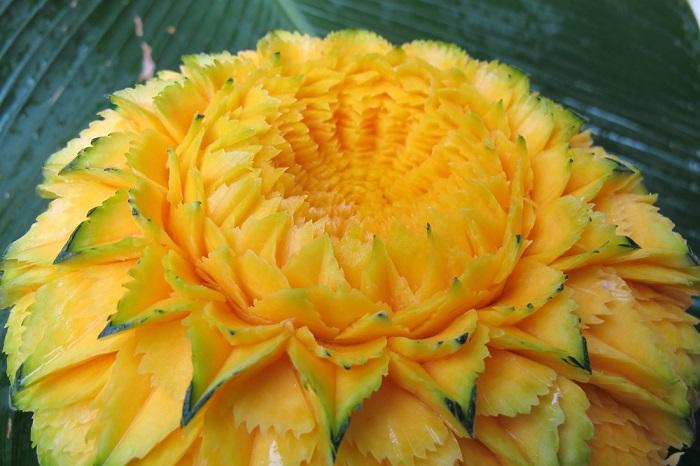 Цветок великолепной красоты расцвел из сердцевины спелой папайи.