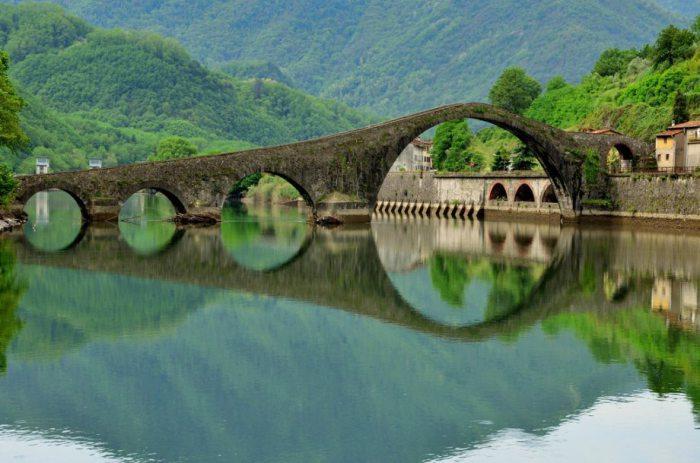Мост поражает своей непривычной формой, а отражение на поверхности реки создает его подводного брата-близнеца.