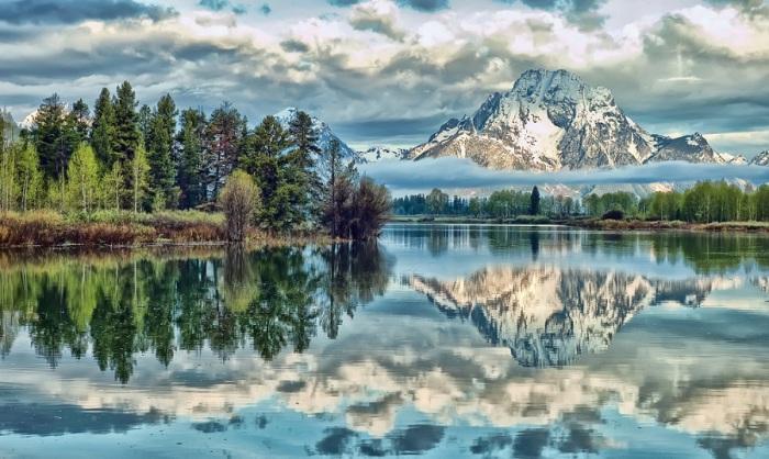 Величественная гора отражается на поверхности озера рядом с небольшим островком.