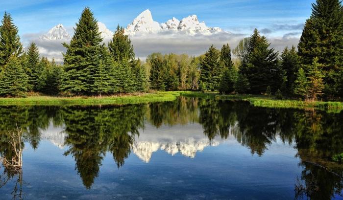 Жаркое лето, бурная зеленая растительность торжествует на берегу озера, но отражение заснеженных горных пиков на воде создает эффект, как будто здесь очень холодно и зябко.