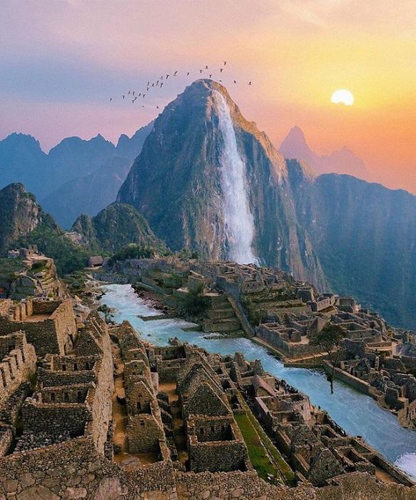 Непрерывные потоки водопада падают с горы Уайна-Пикчу и стремительно несутся по древнему городу Мачу-Пикчу.