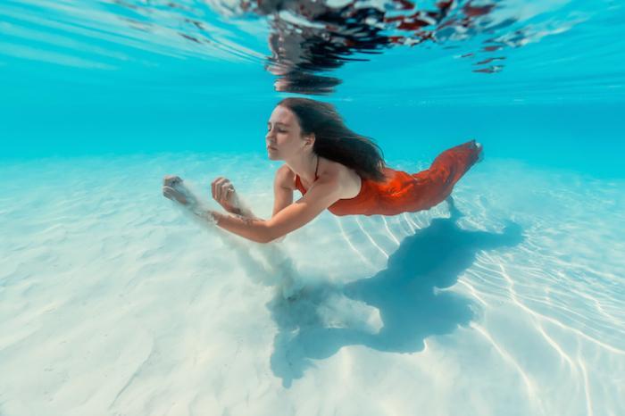 Лазурная вода настолько прозрачна, что позволяет видеть песчинки, которые поднимает Саша с дна океана.