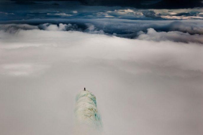 Альпинист Реми МакМертри (Remi McMurtry), стоящий на вершине горы в Исландии.